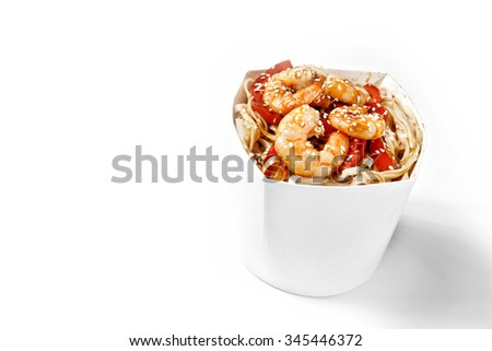 Delicious seafood wok noodles box with shrimps and udon. Chinese and asian takeaway fast food. Studio isolated with real shadow