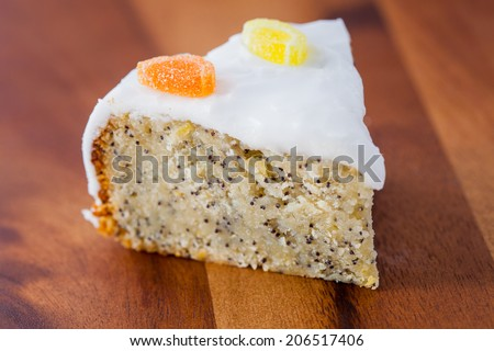 Delicious slice of lemon and almond drizzle cake with poppy seeds and white icing on a wooden board - stock photo