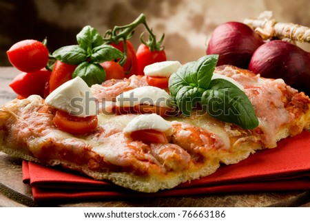 delicious slice of pizza with buffalo mozzarella and cherry tomatoes on wooden table - stock photo