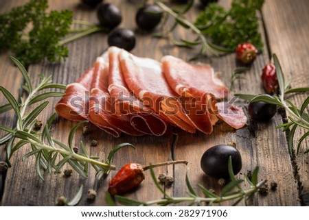 Delicious sliced bacon on wooden table with herbs - stock photo