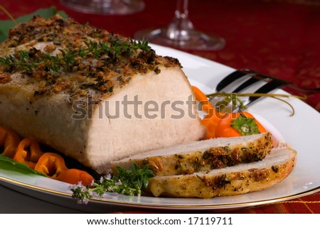 Delicious sliced garlic thyme roast pork loin and glass of red wine ready for Christmas dinner on holiday table. - stock photo