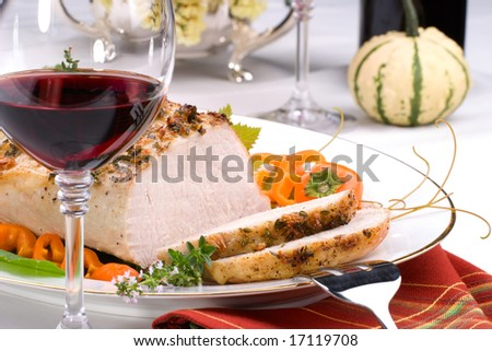 Delicious sliced garlic thyme roast pork loin is ready for dinner in middle of fall arrangement table and two glasses of red wine. - stock photo