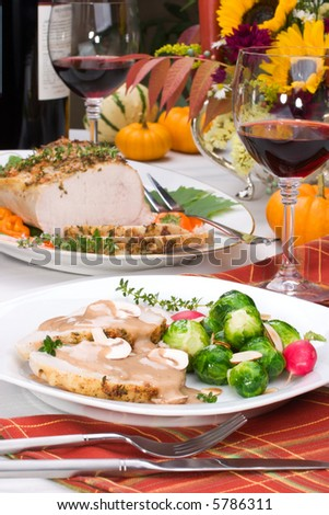 Delicious sliced garlic thyme roast pork loin with mushrooms sauce, brussels sprouts, almonds and radish ready for dinner in middle of fall arrangment table and two glasses of red wine.