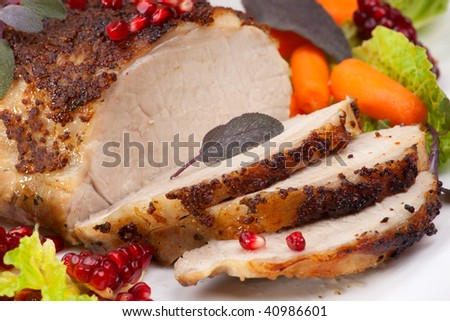 Delicious sliced sage  mustard pork tenderloin with vegetables and pomegranate. - stock photo