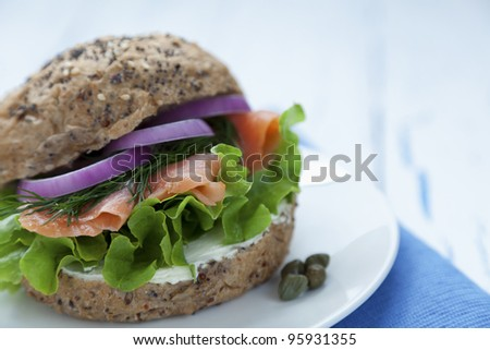 Delicious smoked salmon burger with lettuce, onions, dill and cream cheese