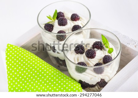 delicious soft cheese dessert with whipped cream and fresh blackberries with a sprig of fresh mint in a glass, in a decorative wooden box on a white table - stock photo