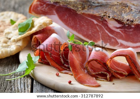 Delicious South Tyrolean bacon, a regional specialty, prepared according to traditional  recipes, often served with the Tyrolean crispy flat bread - stock photo