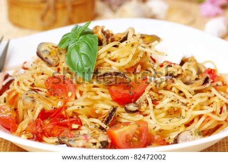 Delicious spaghetti marinara with fish, calamari and mussels with a spicy tomato sauce. - stock photo