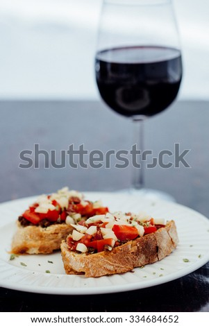 Delicious spanish style toasted bread appetizer with a glass of red wine