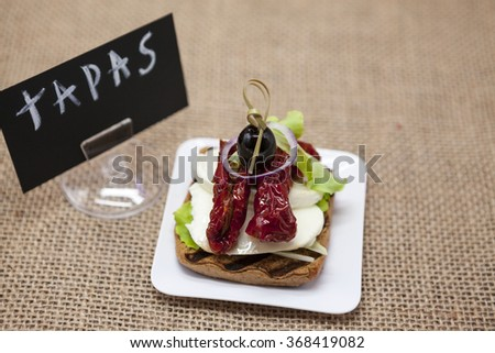 Delicious Spanish tapas, with a rustic mozzarella and dried tomato with olive TAPAS poster .  - stock photo