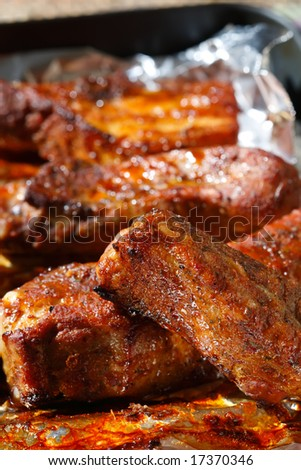 delicious spicy barbeque ribs in roasting tray on foil, shallow DOF