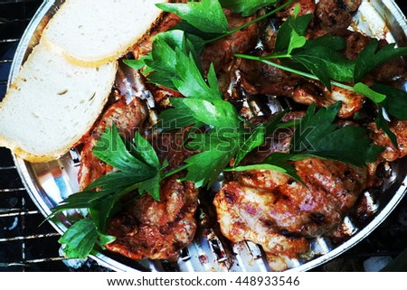 Delicious spicy steak with fresh green herbs and bread roasting on grill during summer barbecue. Closeup view from overhead. - stock photo