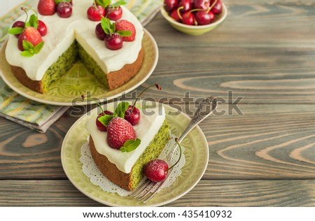 Delicious spinach biscuit cake with cherries and strawberries on wooden background