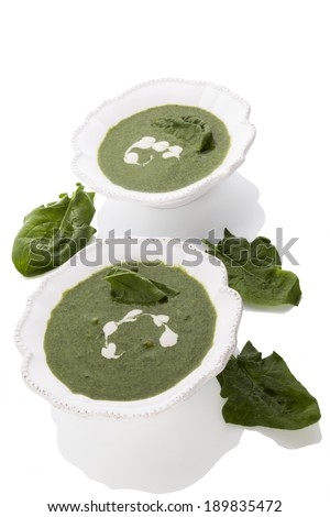 Delicious spinach soup with fresh spinach leaves isolated on white background. Healthy soup eating. - stock photo