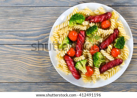 Delicious Spiral Pasta salad with  broccoli, grilled sausages and tomatoes on a  dish, top view - stock photo