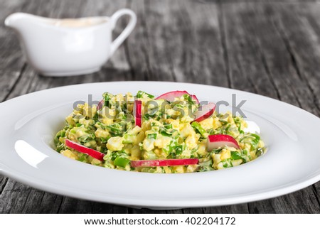 Delicious Spring onion, eggs, radish salad in a white dish on an old rustic wooden table, horizontal close-up - stock photo