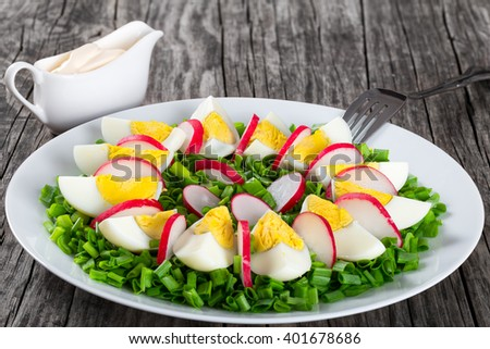 Delicious Spring onion, eggs, radish salad in a white dish with fork and gravy boat with homemade mayonnaise on an old rustic table, horizontal close-up, top view - stock photo