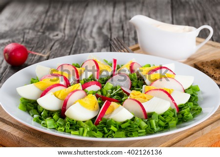 Delicious Spring onion, eggs, radish salad in a white dish with fork on a cutting board with wholegrain crispbread on an old rustic wooden table, horizontal close-up, top view - stock photo