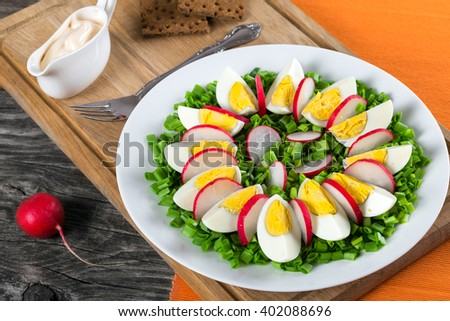 Delicious Spring onion, eggs, radish salad in a white dish with fork on an cutting board on an old rustic wooden table, horizontal close-up, top view - stock photo