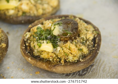 Delicious stuffed mushrooms with breadcrumbs, feta cheese and parsley topped with butter. - stock photo
