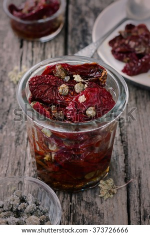 Delicious Sun Dried Tomatoes with Oregano and Capers in a glass jar. Traditional Italian food vegetables. - stock photo