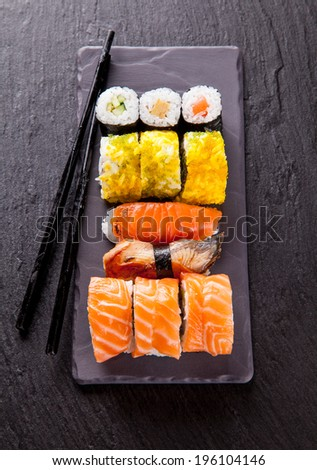 Delicious sushi pieces served on black stone plate with pair of black sticks  - stock photo