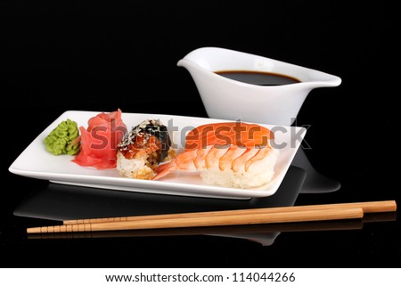 delicious sushi served on plate isolated on black - stock photo