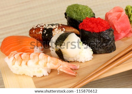delicious sushi served on wooden board on bamboo mat close-up - stock photo