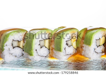 Delicious sushi with avocado topping on rolled seafood and rice arranged in a row on a tray at a sushi bar or on a buffet table at a catered event - stock photo