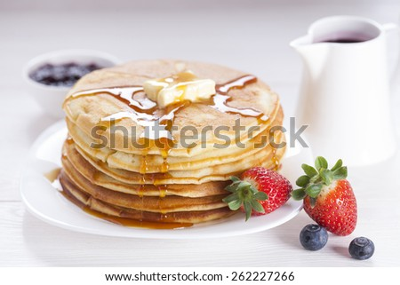 Delicious sweet American pancakes on a white plate with fresh fruits, sauce and side dishes. - stock photo