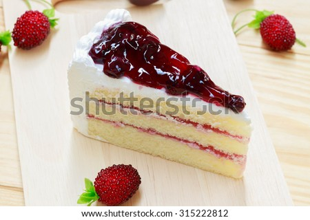 delicious sweet blueberry cheese cake on wooden with strawberry fruit on wood background can use in magazine book or brochure or introduce about ingredient - stock photo