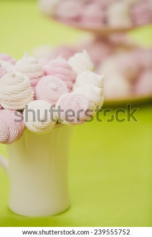 Delicious sweet buffet with homemade pink and white zephyr. Russian marshmallows. On a green background, selective focus - stock photo