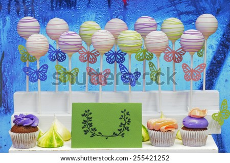 Delicious sweet cake-pops on sticks and cup-cakes - stock photo