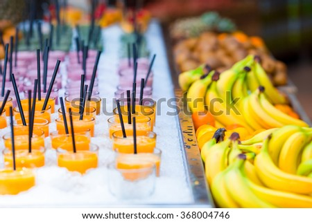 Delicious sweet cocktails and fresh fruits in the shop with takeaway - stock photo