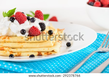 Delicious sweet crepes decorated air-cream and ripe berries, raspberries, blackberries and blueberries on a white plate, bright blue polka dot napkin. Tasty breakfast. - stock photo