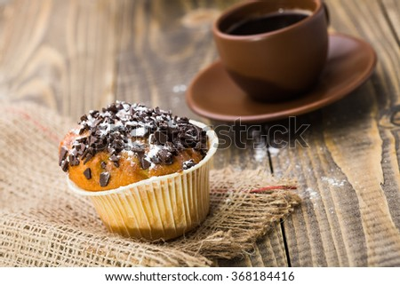 Delicious sweet dessert fattening traditional muffin with chocolate chip food rich of carbohydrates on sackcloth near cup of strong aromatic coffee tasty lunch closeup on wooden background, horizontal - stock photo