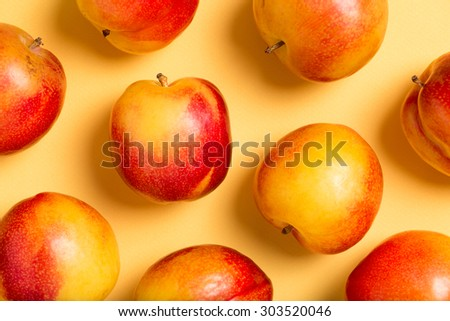 delicious, sweet, organic plums in red and yellow, isolated on a yellow craft paper background, top view, close up, horizontal - stock photo