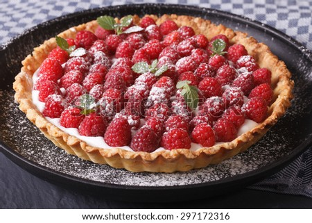 Delicious tart with fresh raspberries and mint on a plate close-up horizontal