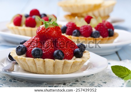 Delicious tartlets with fruit and cream mascaropne on plate - stock photo