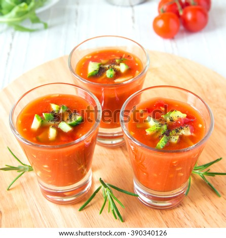 delicious tasty cold tomato soup gazpacho in portion glasses on wooden board, closeup, vertical - stock photo