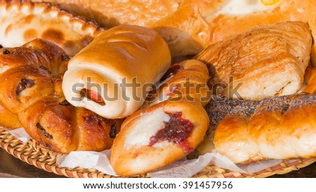 delicious tasty pie with sausage and sweet blush buns and cakes with jam on straw plate - a traditional Russian style