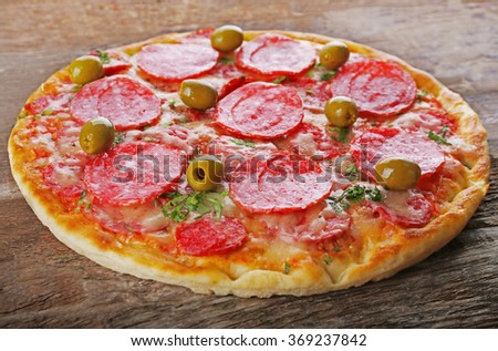 Delicious tasty pizza on wooden background
