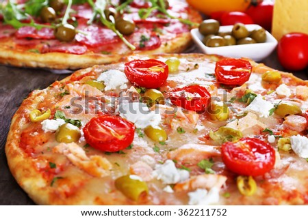 Delicious tasty pizzas with ingredients on table, closeup - stock photo