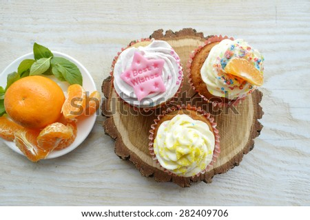 delicious, tender, tasty cupcakes with tangerine,decorated with mint leaves and star anise on a wooden tray - stock photo