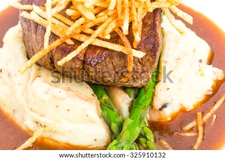 Delicious tenderloin steak with asparagus and french fries on potato puree. Macro. Photo can be used as a whole background.