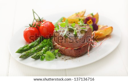 Delicious thick portion of grilled fillet steak served with fresh green asparagus spears, potato and tomato