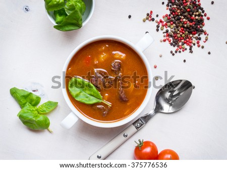Delicious tomato soup with meat on a white rustic wooden table with fresh cherry tomatoes, basil leaves and dry pepper. Ingredients for soup. Top view - stock photo