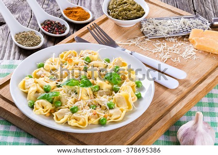 Delicious tortellini with green peas, fried Pine nuts, decorated with basil leaves on a white dish with spice, sauce pesto and parmesan cheese on an old rustic table, italian style. close-up - stock photo