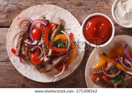 Delicious tortillas stuffed with meat and vegetables close-up. horizontal view from above
