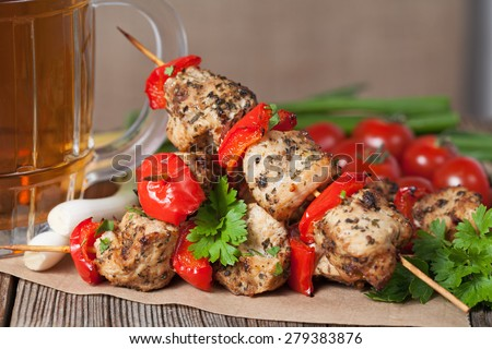 Delicious traditional chicken or turkey kebab skewer barbecue meat with vegetables, green onion and beer on bamboo sticks. Served on kitchen table background. Rustic style, natural light. - stock photo